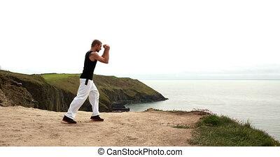 Fit man practicing martial arts overlooking the ocean