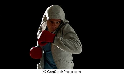 Fit man punching with boxing gloves on black background in...