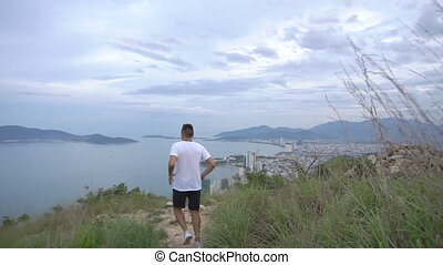Fit man runner happy and celebrating success. Male stand on top of the mountain, cheering in winning gesture. Beautiful view of Nha Trang city, Vietnam