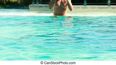 Fit man swimming in outdoor pool