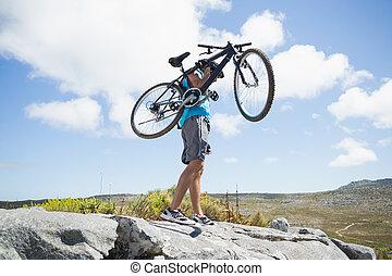 Fit man walking on rocky terrain holding mountain bike on a...