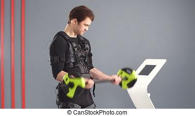 Fit Man wearing black electrostimulation suit lifting...