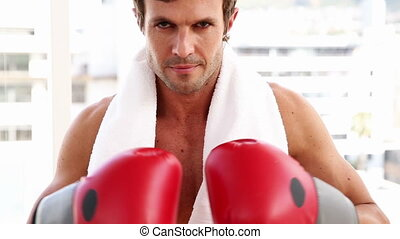 Fit man wearing boxing gloves looking at camera at the gym