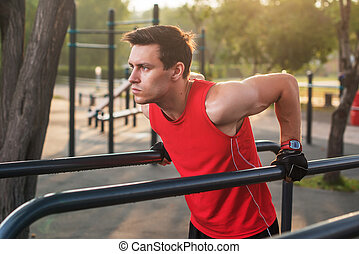 Fit man workout out arms on dips horizontal bars training...