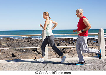 Fit mature couple jogging together on the pier
