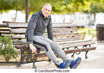 Fit mature man exercising outdoors on a park bench