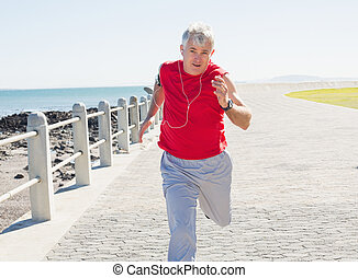 Fit mature man jogging on the pier