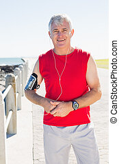 Fit mature man smiling at camera on the pier