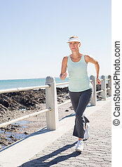 Fit mature woman jogging on the pier
