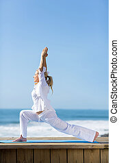 fit mature woman yoga pose on beach - side view of fit...