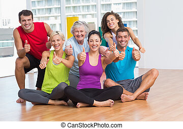 Fit men and women gesturing thumbs up in fitness studio
