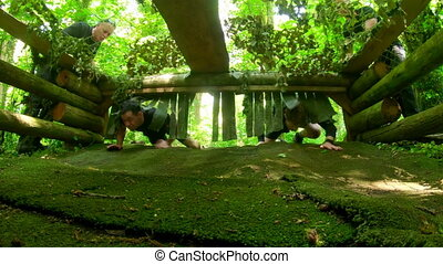 Fit men crawling under the net during obstacle course 4k - ...