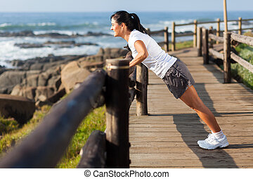 fit middle aged woman exercising at beach