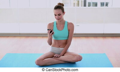 Fit model sitting on exercise mat sending a text in a bright...