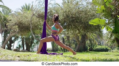 Fit muscular gymnast warming up in a park