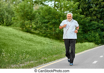 Fit old man running on racetrack in green park.