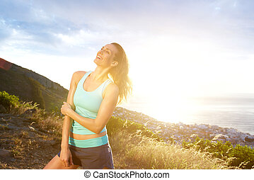 Fit older woman smiling outdoors at sunset