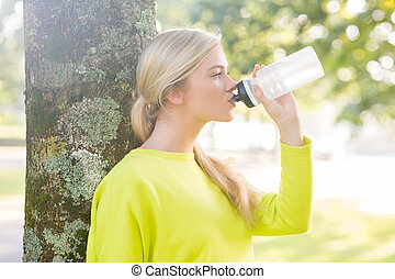 Fit peaceful blonde drinking from water bottle in a park on...