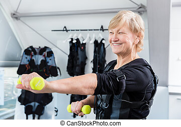 Senior lady staying fit with dumbbell exercise in wireless ems gym