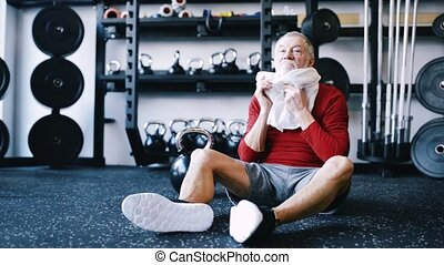 Fit senior man in gym sitting on the floor, wiping sweat of his face