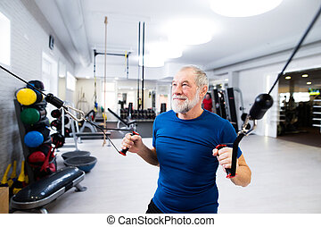 Fit senior man in gym working out with weights.
