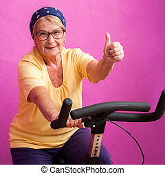 Fit senior woman doing thumbs up on bicycle.