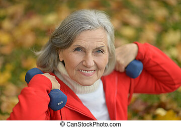 fit Senior woman exercising with dumbbells