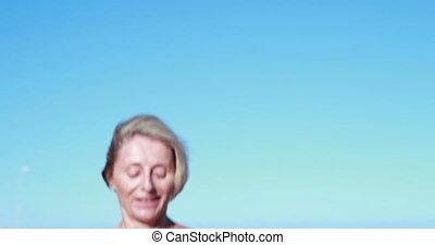 Fit senior woman pausing on her run