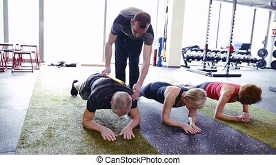 Fit seniors in gym in plank position with their trainer