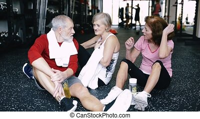 Fit seniors in gym sitting on the floor, resting, discussing fitness progress