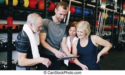 Beautiful fit seniors in sport clothing in gym with their personal trainer discussing fitness plan. Sport fitness and healthy lifestyle concept.