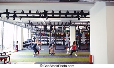 Fit seniors in gym with personal trainer doing various exercises
