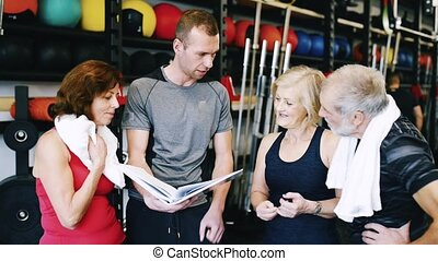 Fit seniors in gym with personal trainer discussing fitness plan