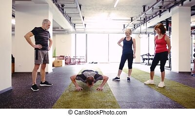 Fit seniors in gym with their trainer doing push up