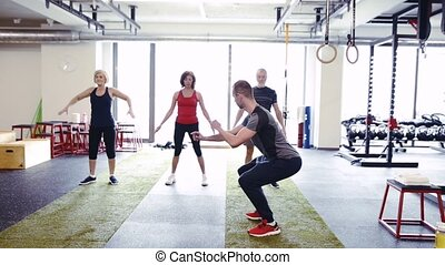 Fit seniors in gym with their trainer doing squats