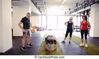 Fit seniors in gym with their trainer in plank position