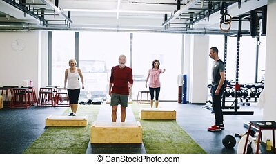 Fit seniors in gym working out, doing box steps.