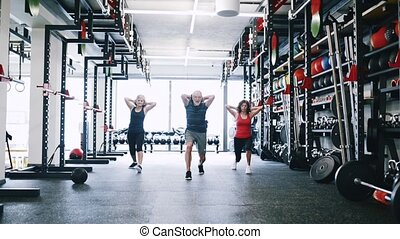 Fit seniors in gym working out, doing lunges