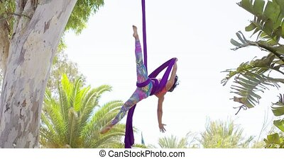 Fit shapely female gymnast working out on ribbons