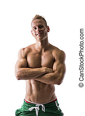 Fit shirtless male model posing with a lot of confidence, arms crossed