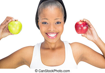 Fit smiling woman holding red and green apple while looking at camera against white background