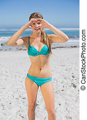 Fit smiling woman in bikini on the beach making heart shape with