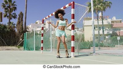 Fit smiling woman in roller skates - Young fit female in...