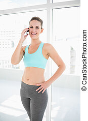 Fit smiling woman in sportswear talking on the phone