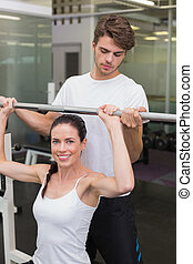 Fit smiling woman lifting barbell with her trainer spotting