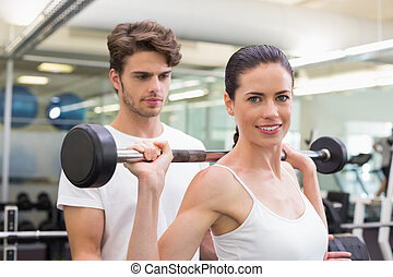 Fit smiling woman lifting barbell with her trainer