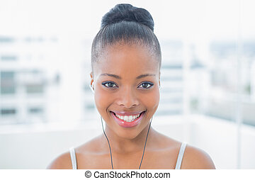 Fit smiling woman listening to music