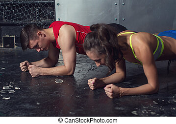 fit sportive man and woman doing plank core exercise training back press muscles concept gym sport sportsman crossfit fitness workout strenght power