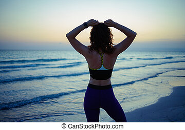 fit sports woman on ocean shore in evening adjusting hair
