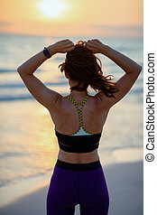 fit sports woman on seacoast at sunset adjusting hair